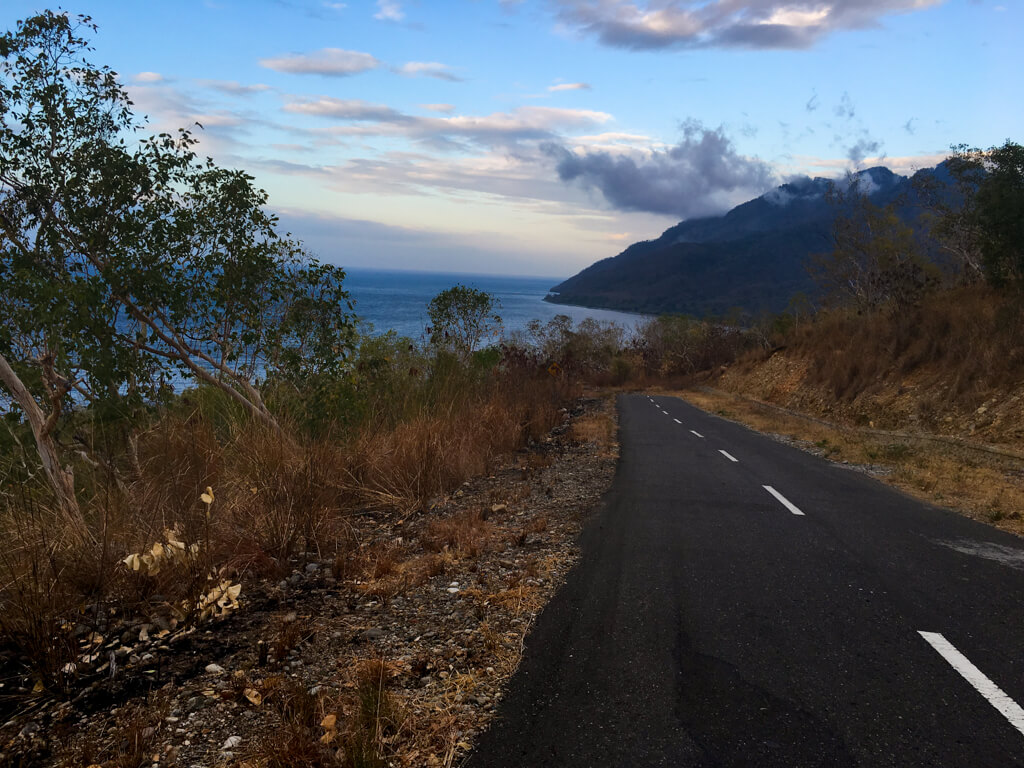 A road descending with the Banda sea in front.