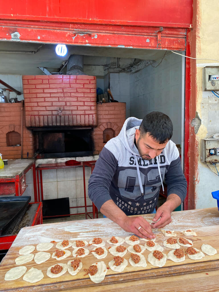A local man makes sfeeha in front of a brick oven