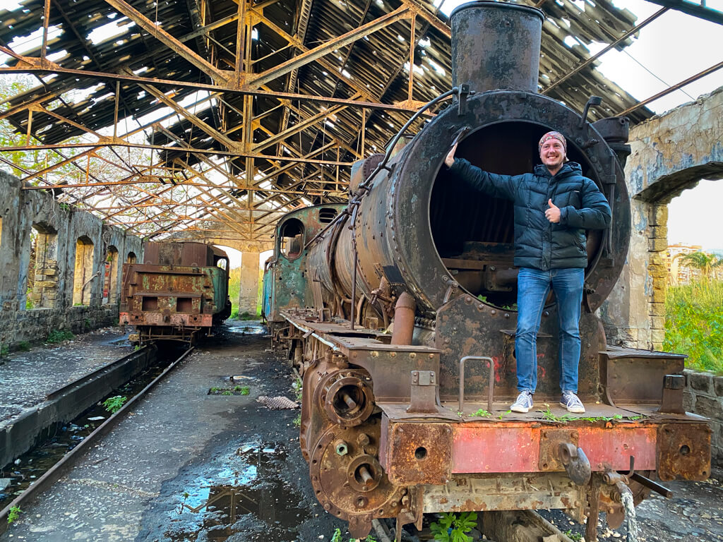 Me, standing on the front of a locomotive in a run down railway building.