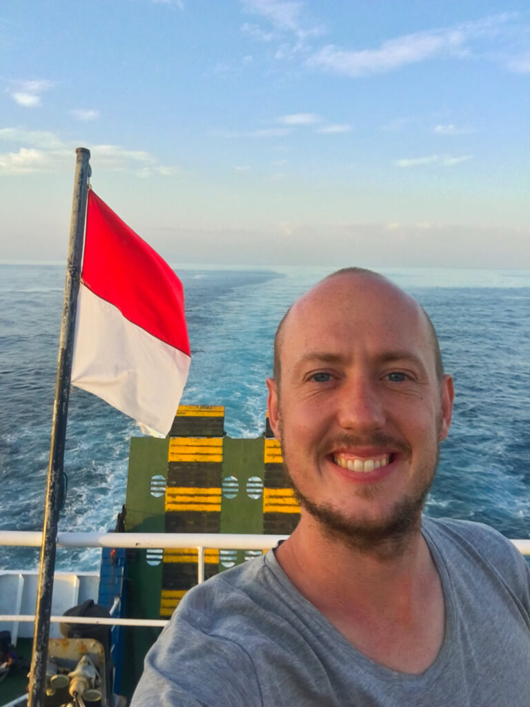 Me, standing on the ferry in the evening with an Indonesian flag blowing in the wind.