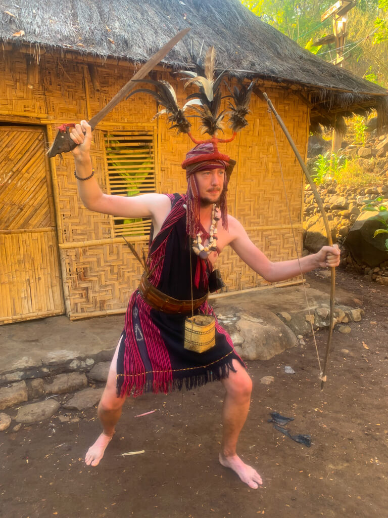 Me, dressed in traditional costume, with a sword in one hand and a bow in the other.