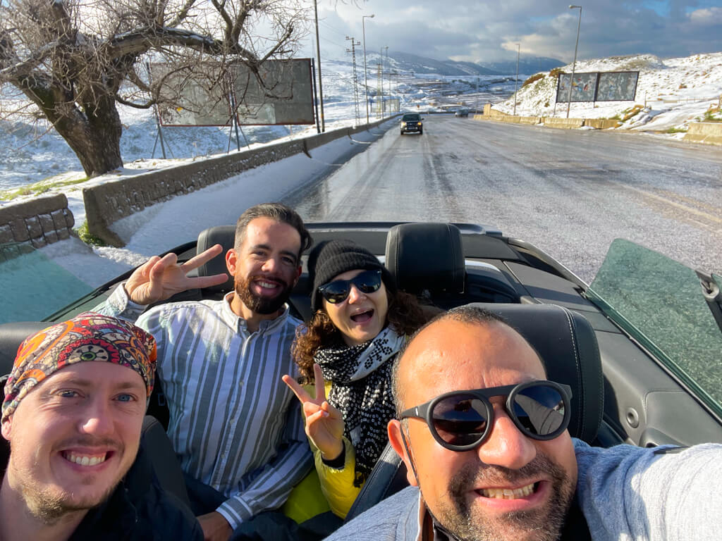 The four of us in our convertible car speeding over the mountains with snow on the ground