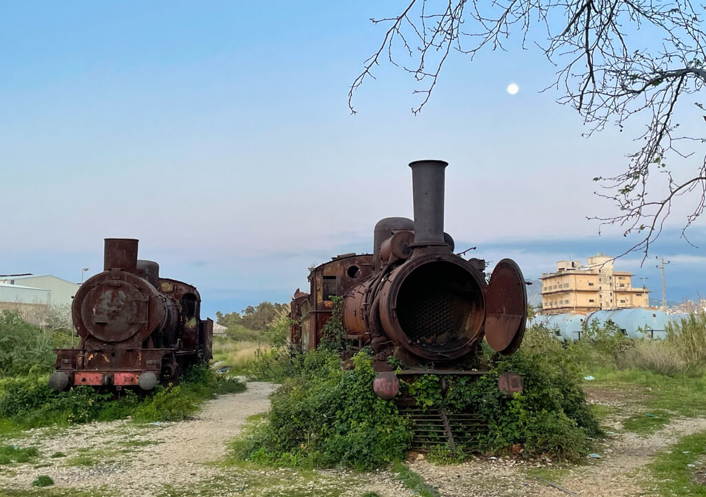 Two old locomotives rusting outdoors under the moon at dusk
