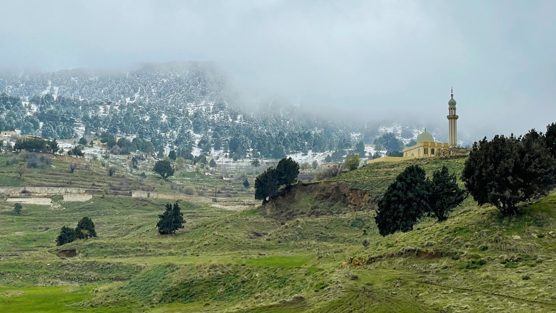 Green pastures with another mountain covered in snow rising in the distance and a mosque standing on a small hill in front.