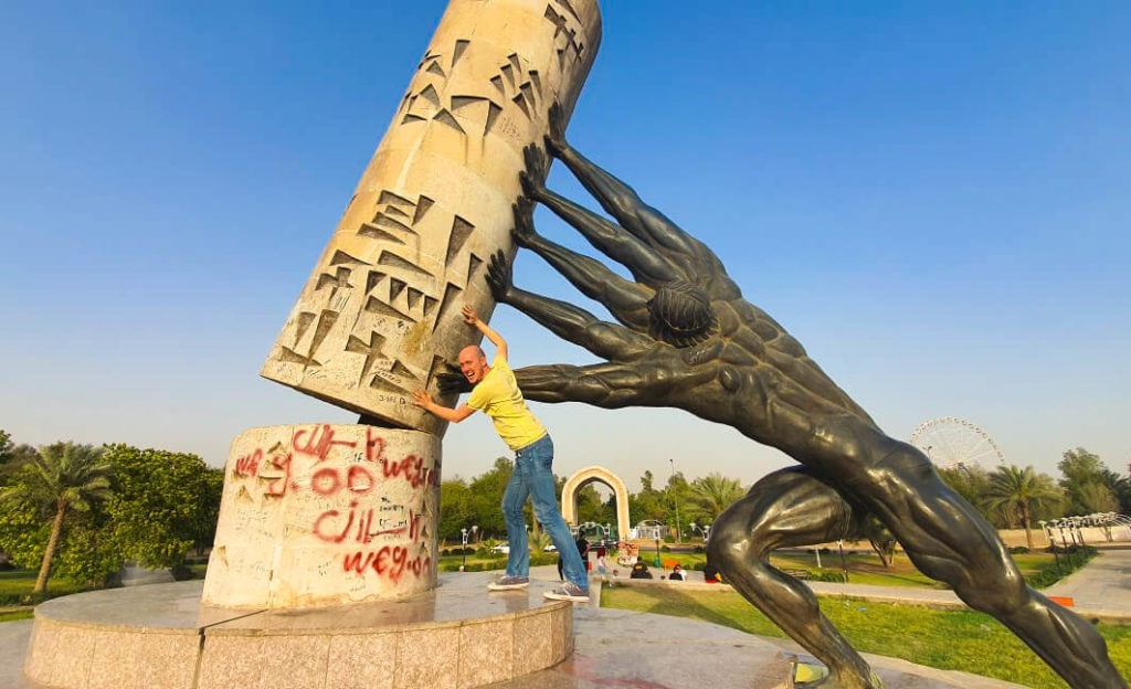 My at the Saving Iraqi Culture monument in Baghdad, pushing against 'culture' to help support it, along with a man with four arms (part of the statue).