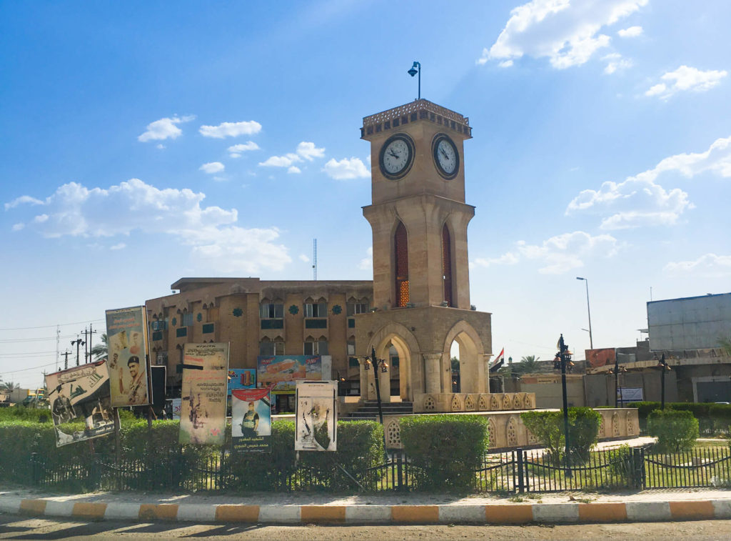 A square with a clock tower and Arabic signs around it.