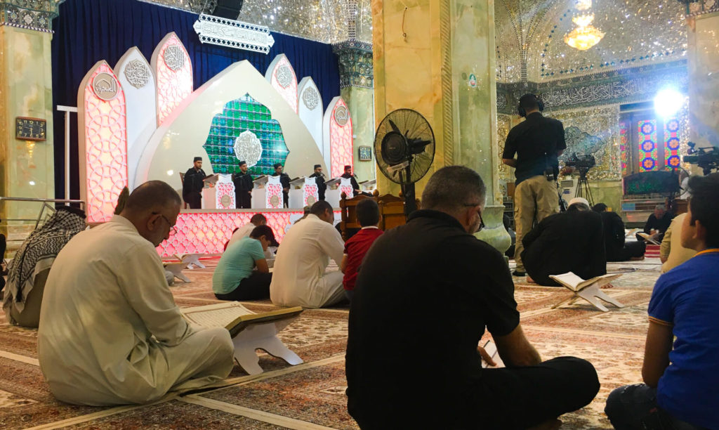 Religious figures reading prayers in the Al-Askari mosque while people pray.