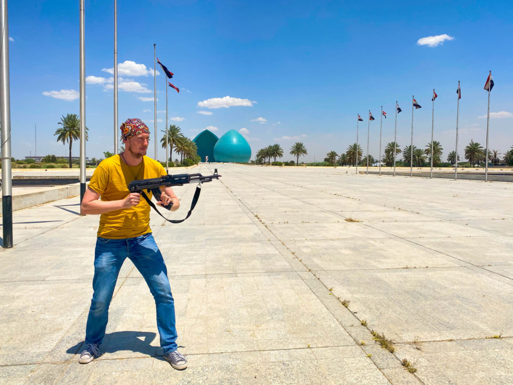 Me holding a Kalashnikov in front of the Martyr's Monument in Baghdad.