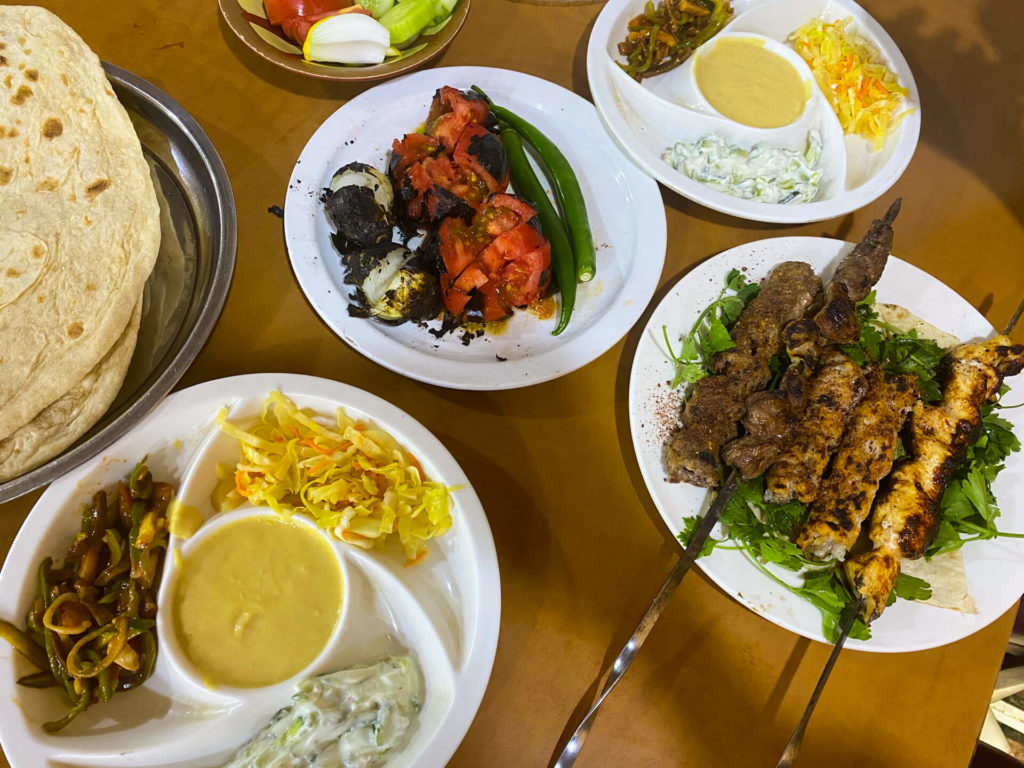 Kebab and other food, including humous and vegetables.