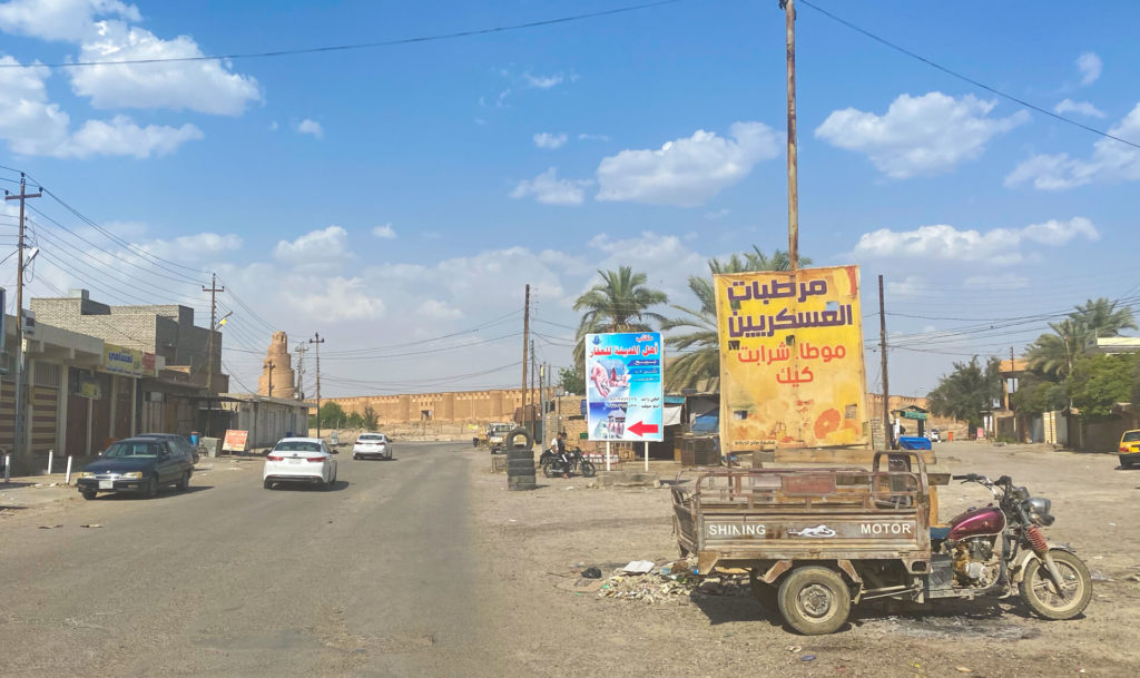 A random road with an old motorbike cart parked on the side with the Malwiya minaret in the background.