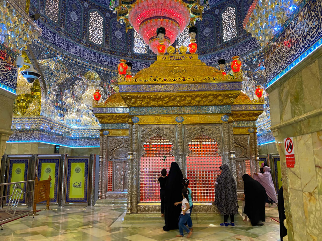 Women walking through the colourful interior of the mosque past the tomb of an imam.