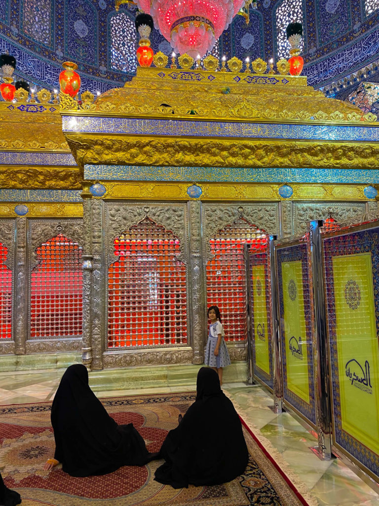 A little girl standing by the tomb of an imam in the colourful Al-Askari mosque.