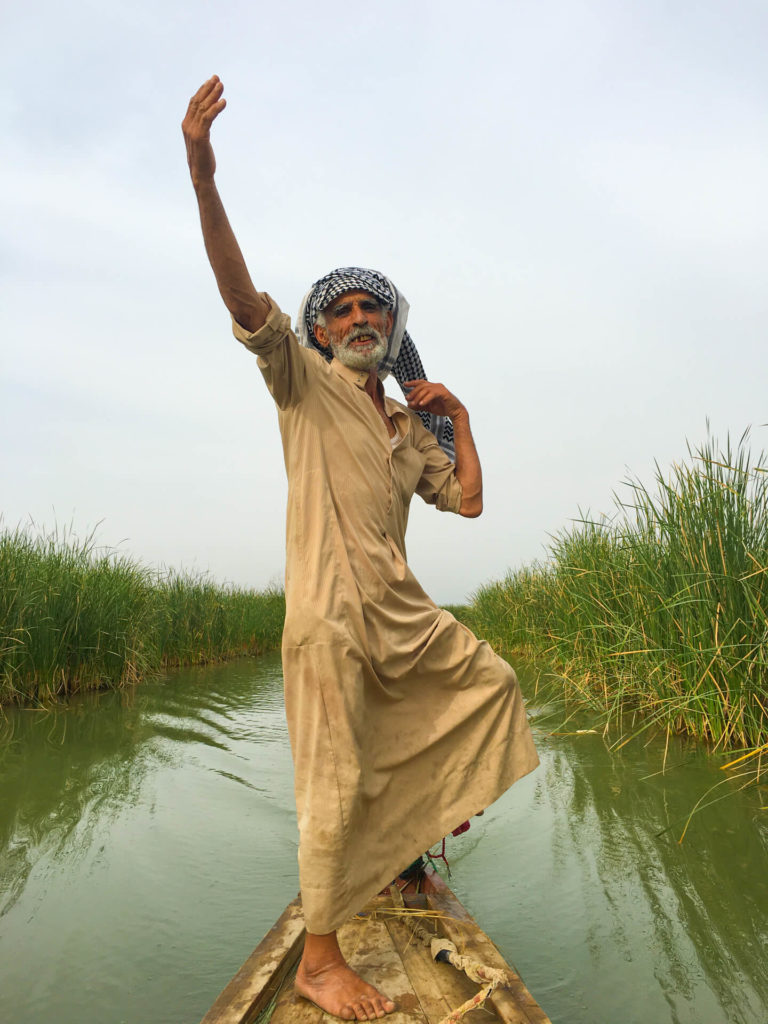 Our boatman standing in the boat and waving his arms in the air.