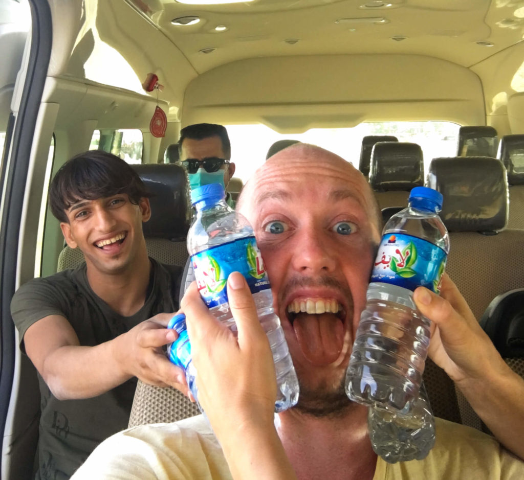 Me with water bottles being held to my face to cool me down and an Iraqi kid grinning from ear to ear behind me.