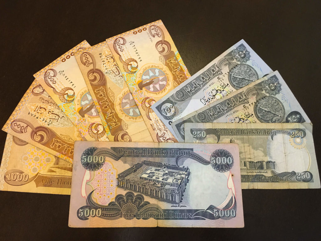 Several Iraqi dinar notes spread out on a table