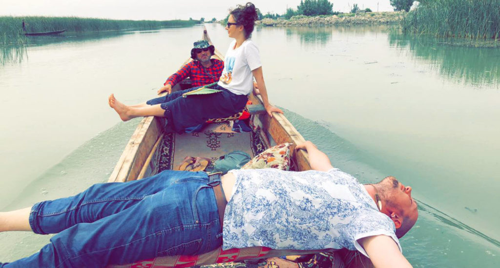 Me lying across a boat in the Mesopotamian marshes with Anna in the background.