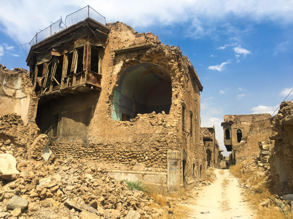 A narrow road winds between bombed out buildings in Mosul's old town.