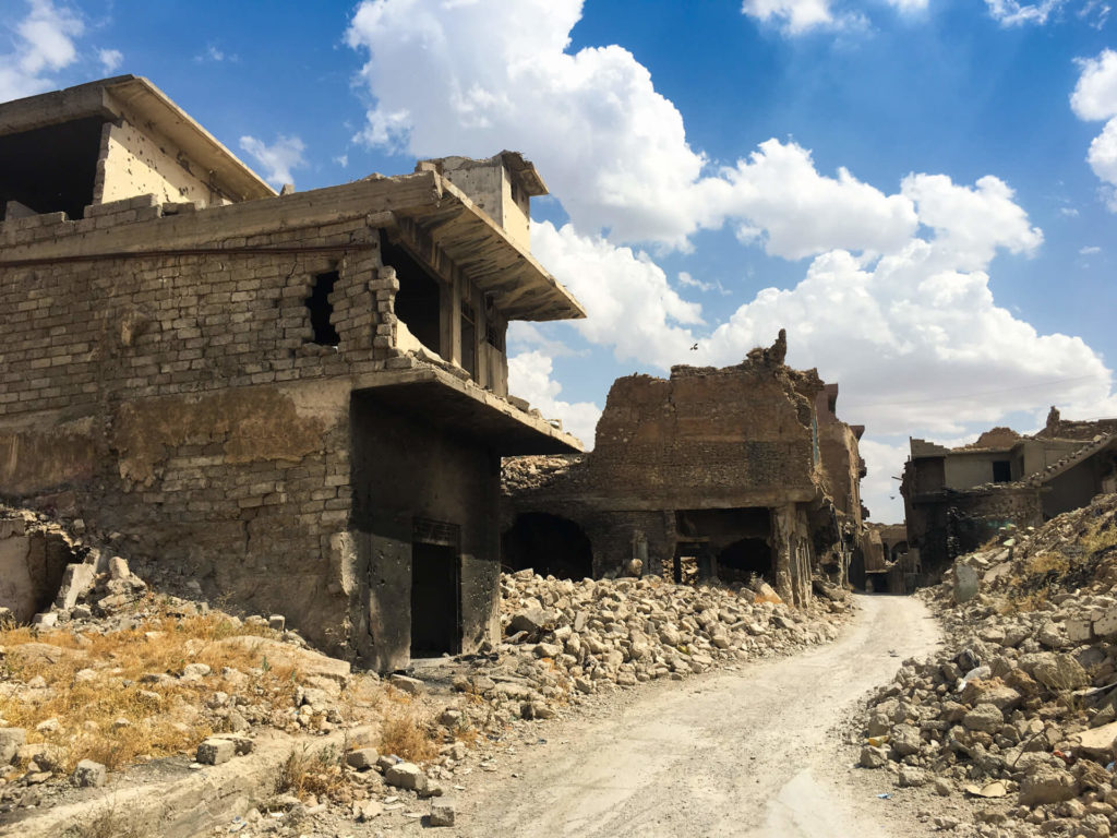 A narrow road winds between bombed-out buildings in Mosul's old town.