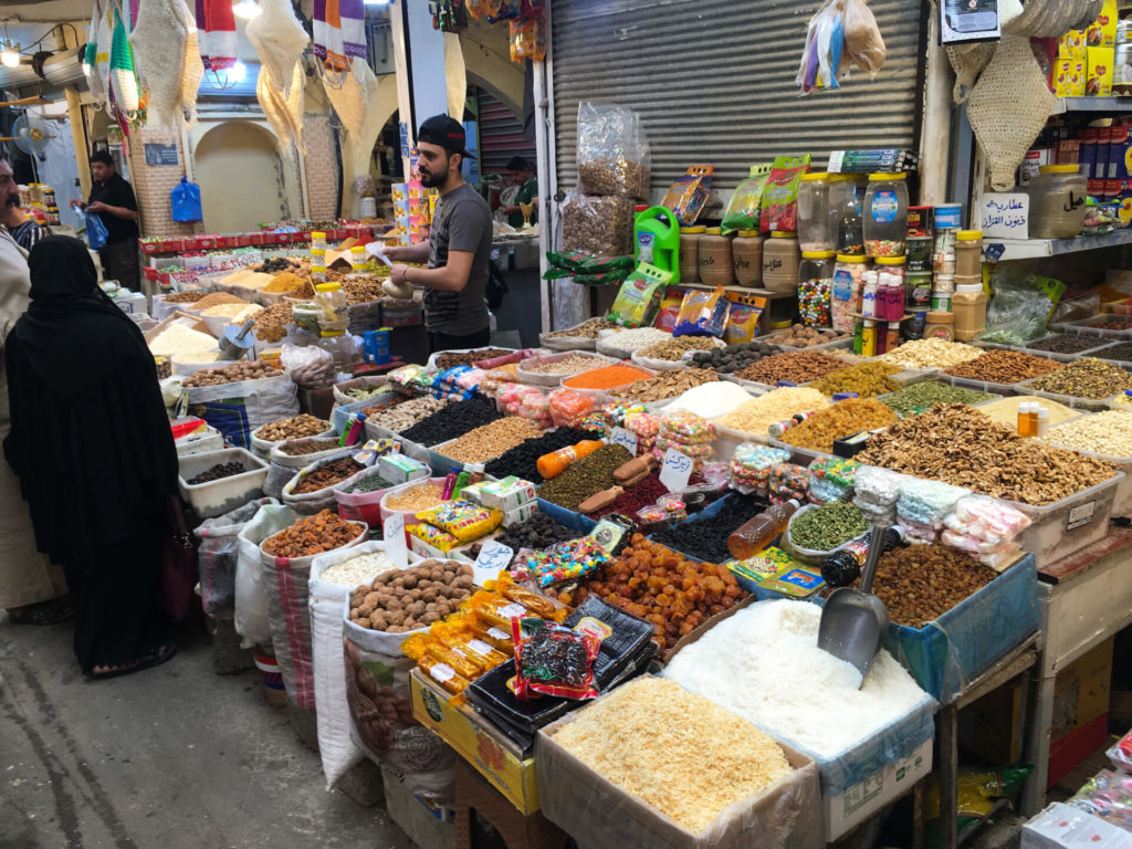 A vendor selling spices talks to an Iraqi woman in full abaya next to his colourful wares.