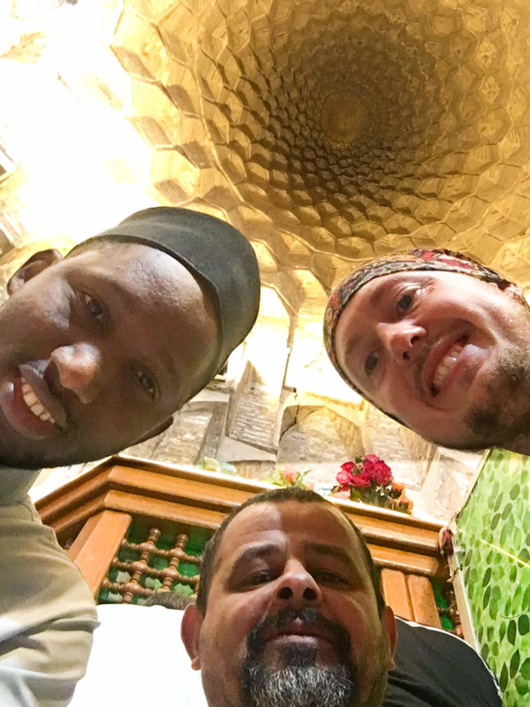Me and two local visitors taking a selfie in the E Radeshams mosque with the inside of the dome in above us.