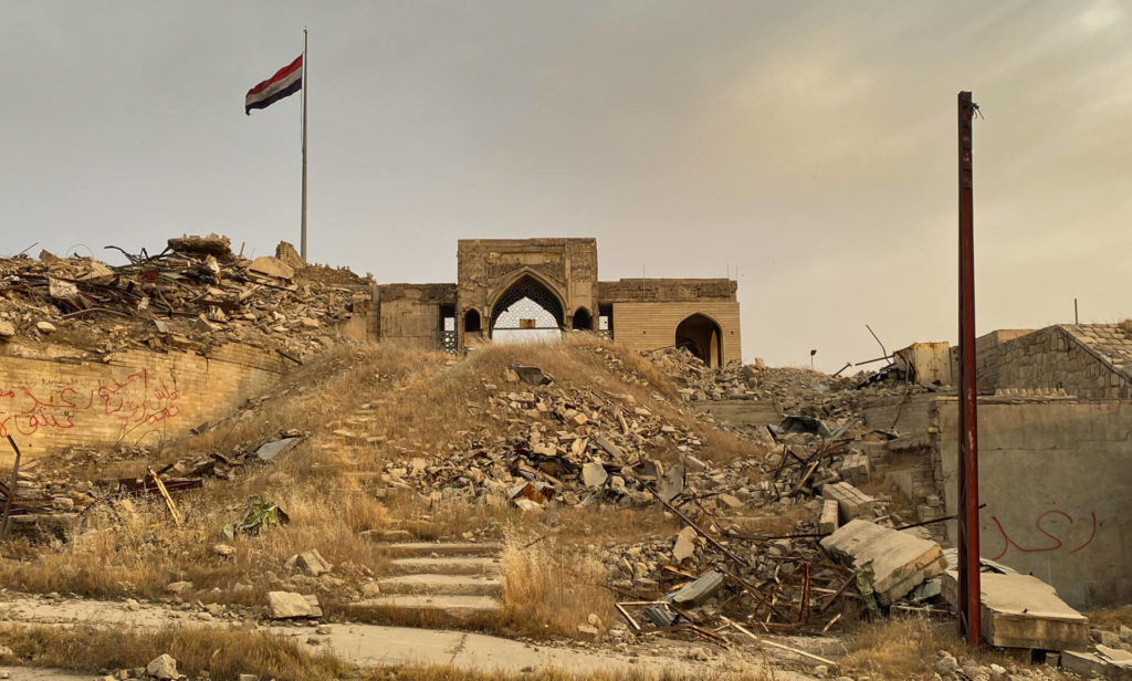 An Iraqi flag flies over the entrance to the mosque at the top of some steps.  Rubble is strewn across the surrounding area.