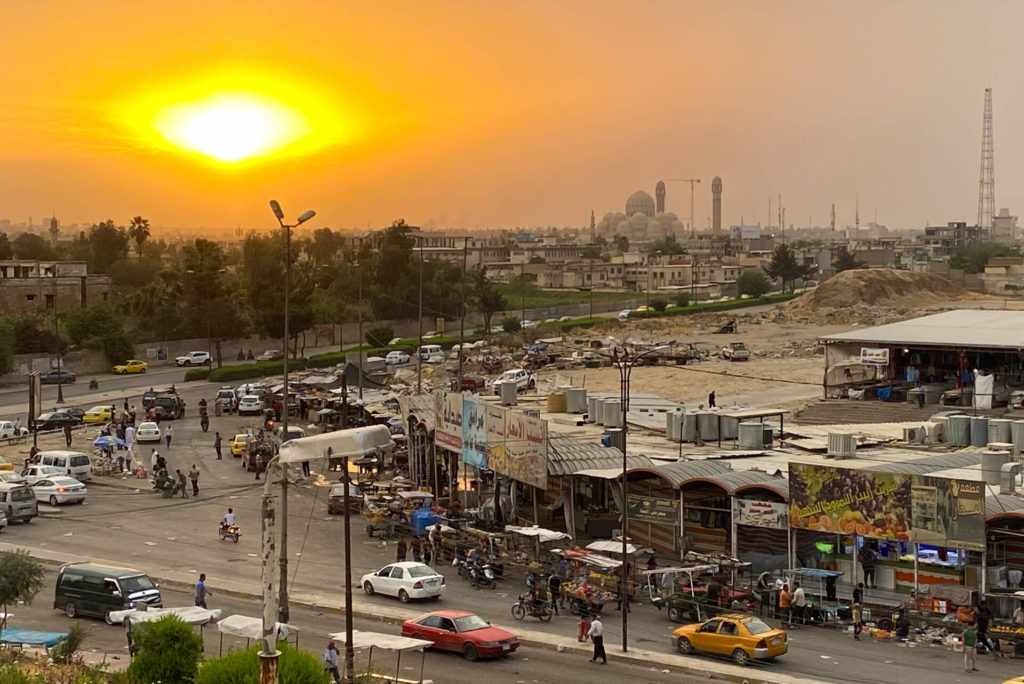 A market in Mosul at sunset with the Mosul Grand Mosque in the background.