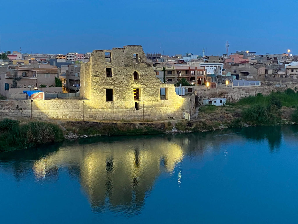 A historic-looking building lit up by the banks of the Tigris.