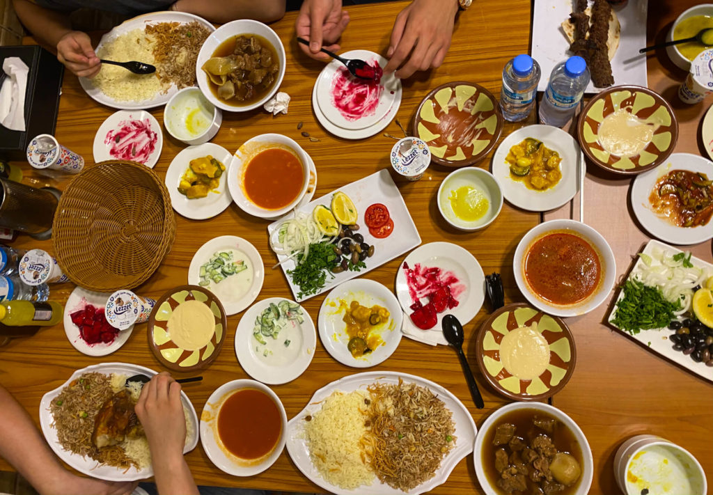 A table spread with many different and very colourful Iraqi dishes.