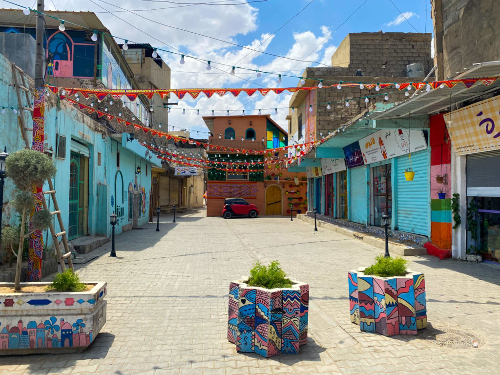 A brightly coloured street in Mosul with blue walls and red bunting hanging across the street.