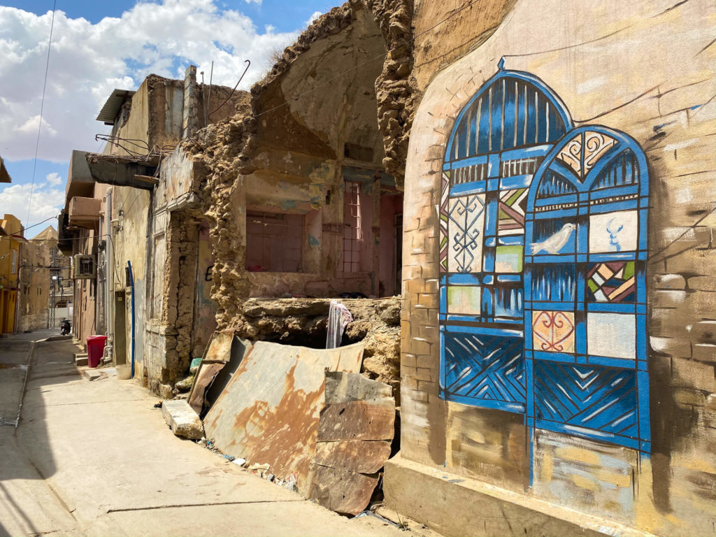 Blue graffiti next to a ruined building in Mosul's old town.