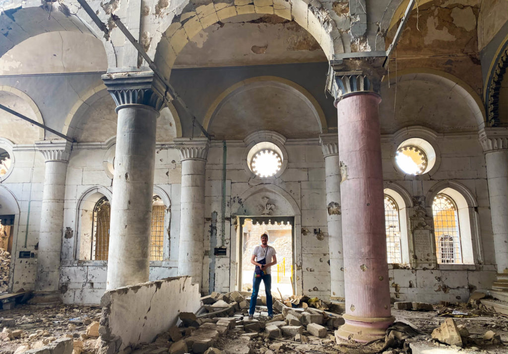 Me standing among the rubble of a badly damaged church in Mosul.  The building still stands, but some of the walls are destroyed.