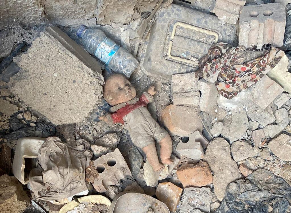 A doll lying among rubble.