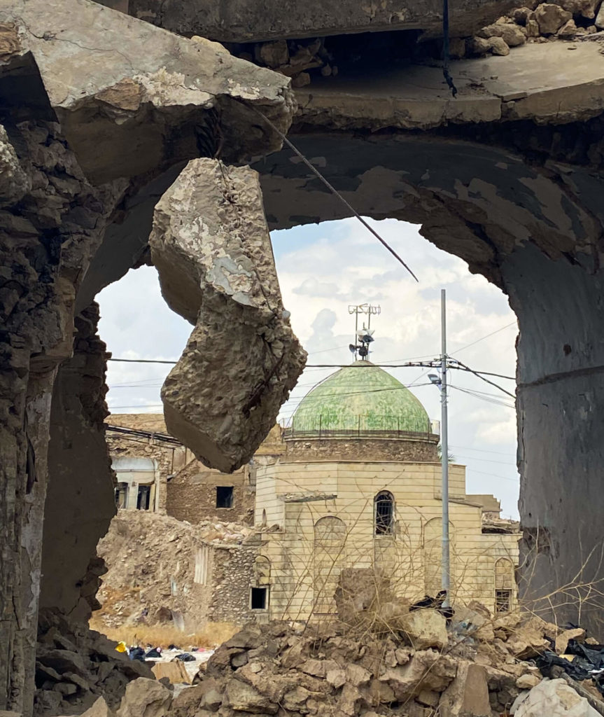 The green dome of the Umayyad Mosque seen through a hole in the wall of a building in the old town of Mosul.