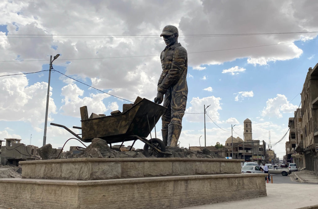 A metal statue of a construction worker with a wheelbarrow full of rubble.