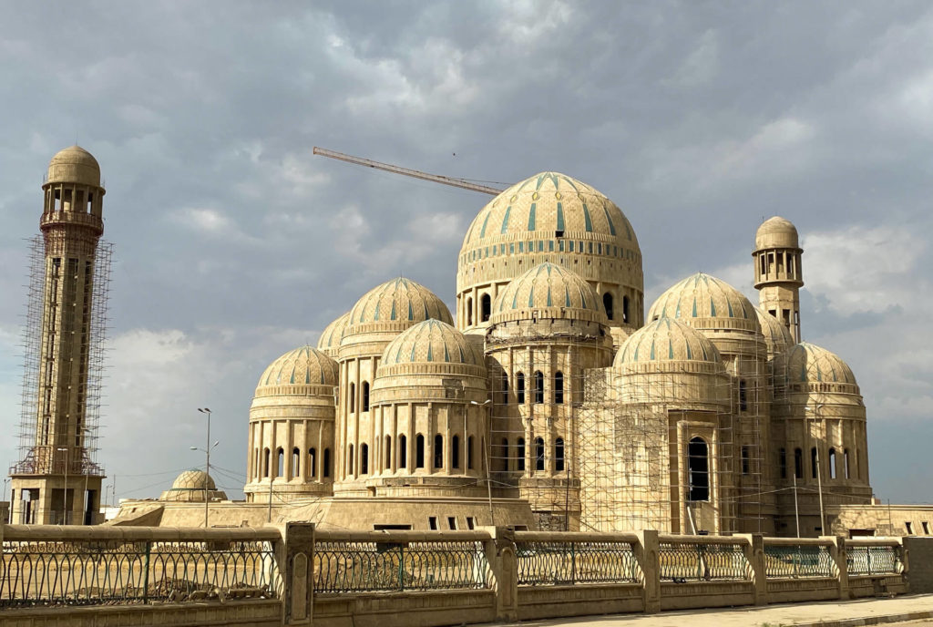 The multi-domed Mosul Grand Mosque with a crane in the background and scaffolding visible on one of its minarets.