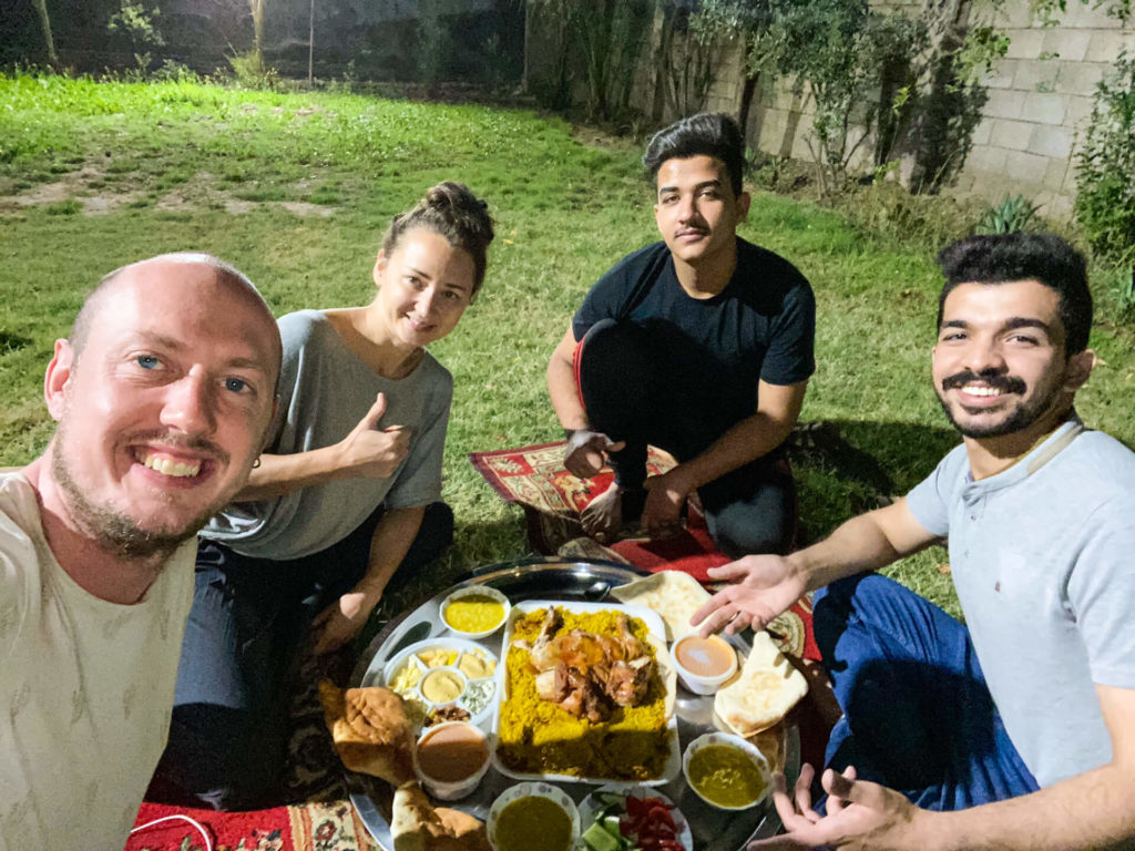 Me, Anna, Haydir and his brother eating dinner on carpets in the garden of Haydir's family's house.