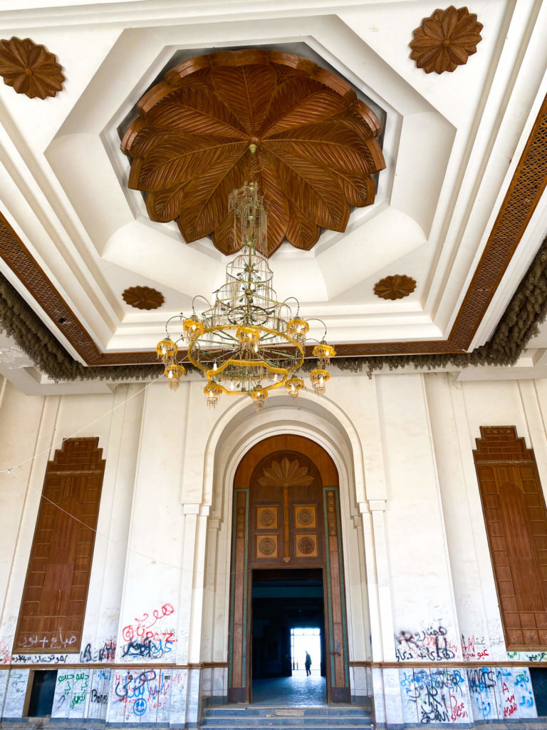 A huge room inside the palace with wooden panelling and a chandelier.