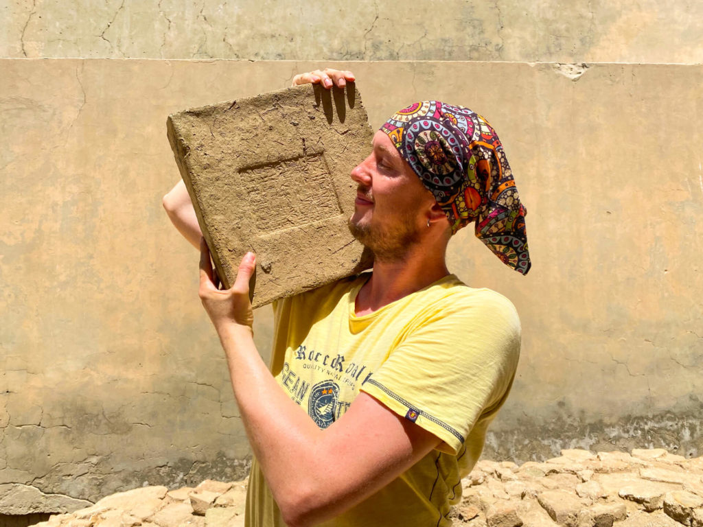 Me, hold a brick with ancient writing on it on my shoulder.
