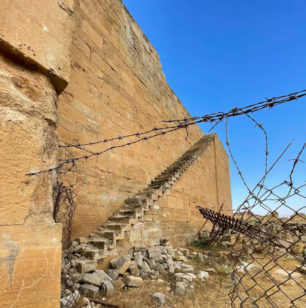 A staircase runs steeply up the side of the ancient walls of Hatra with barbwire in the foreground.