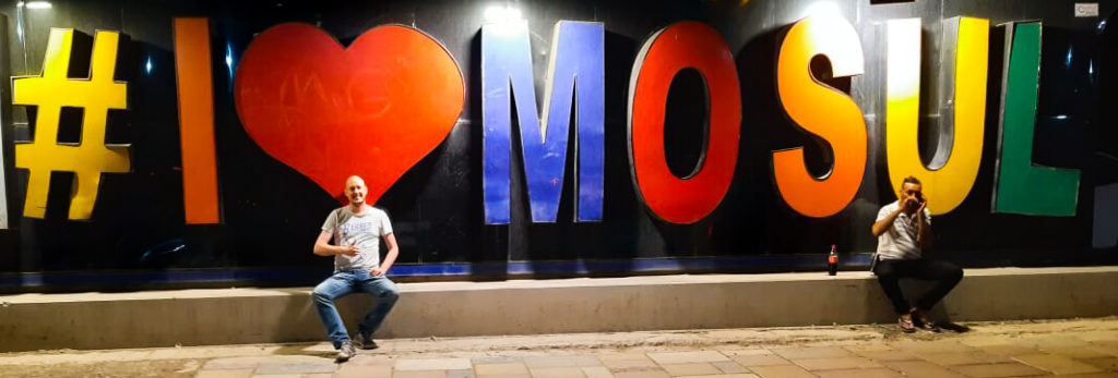 The I Love Mosul sign, with each letter in different colours, and me and a random guy sitting in front.